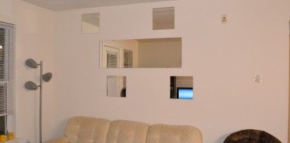 An arrangement of mirrors over our seating area.