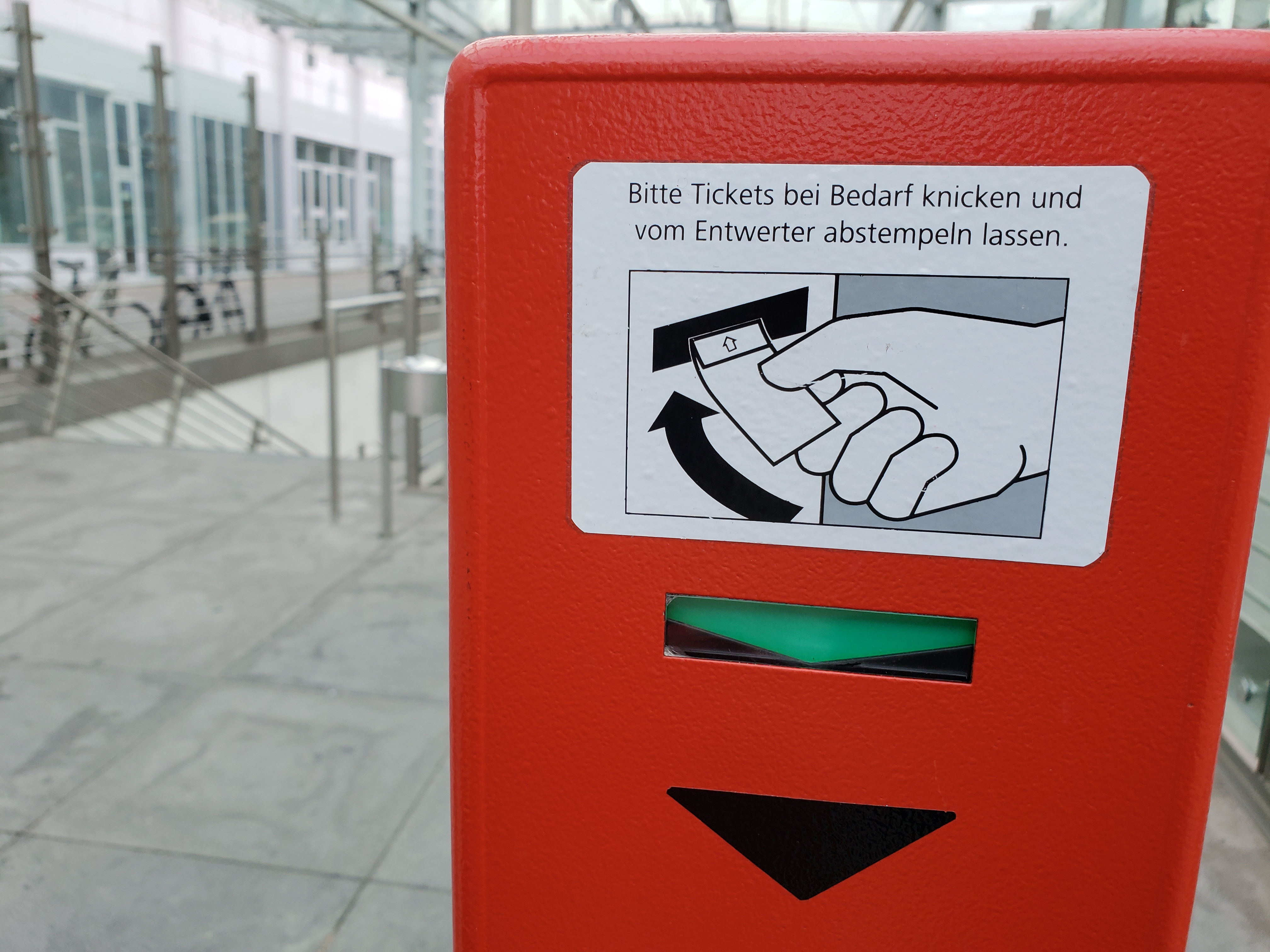 A small stand with German instructions for (maybe) how to flatten a wrinkled public transit ticket.